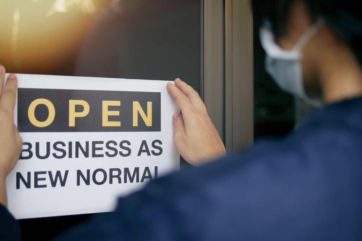 """Reopening for business adapt to new normal in the novel Coronavirus COVID-19 pandemic. Rear view of business owner wearing medical mask placing open sign """"OPEN BUSINESS AS NEW NORMAL"""" on front door."""